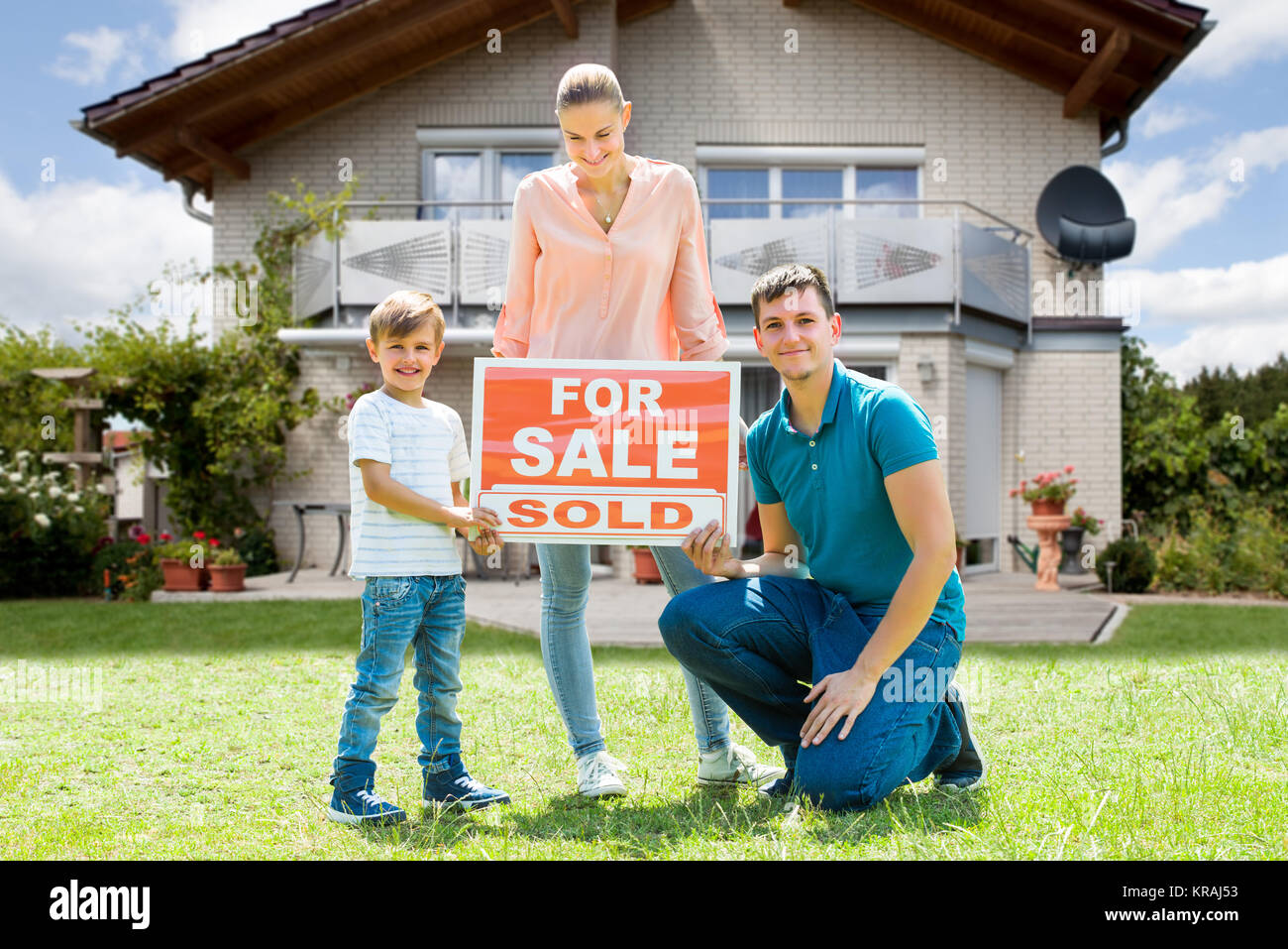Family With A Sale Sign Outside Their Home - Stock Image