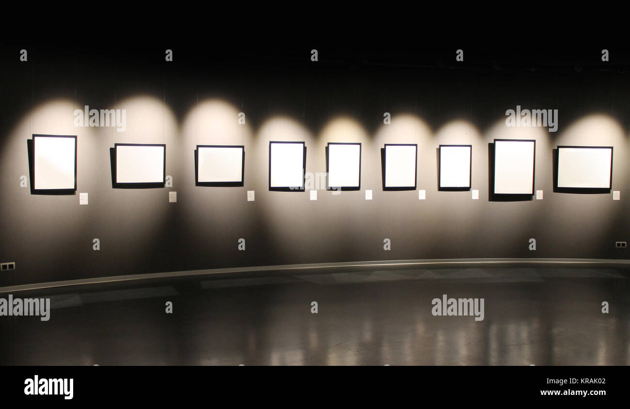 Black wall with empty frames for photos. - Stock Image