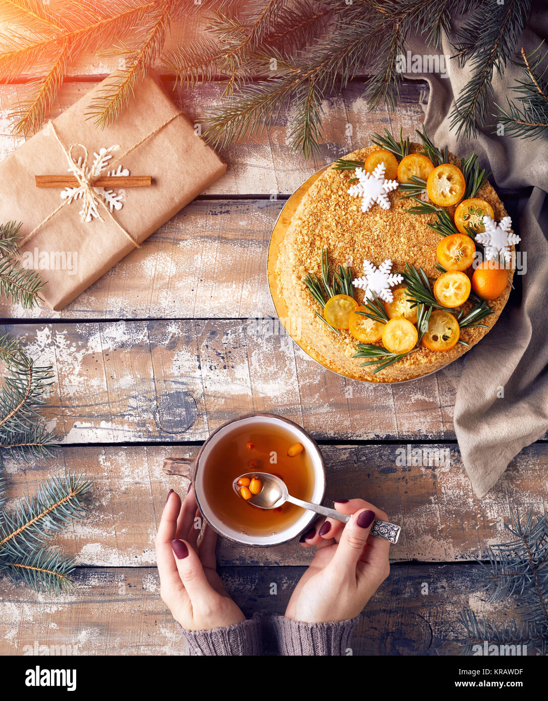 Christmas Honey cake on the table. Woman holding tea with berry near decorated present at breakfast. Stock Photo