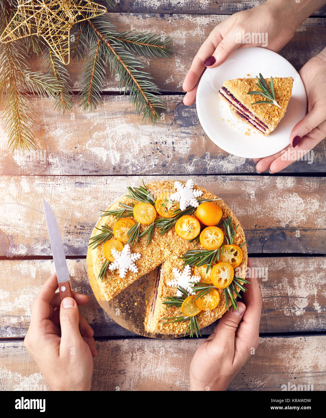 Man cut Christmas Honey cake and woman holding piece on the plate at breakfast. Stock Photo