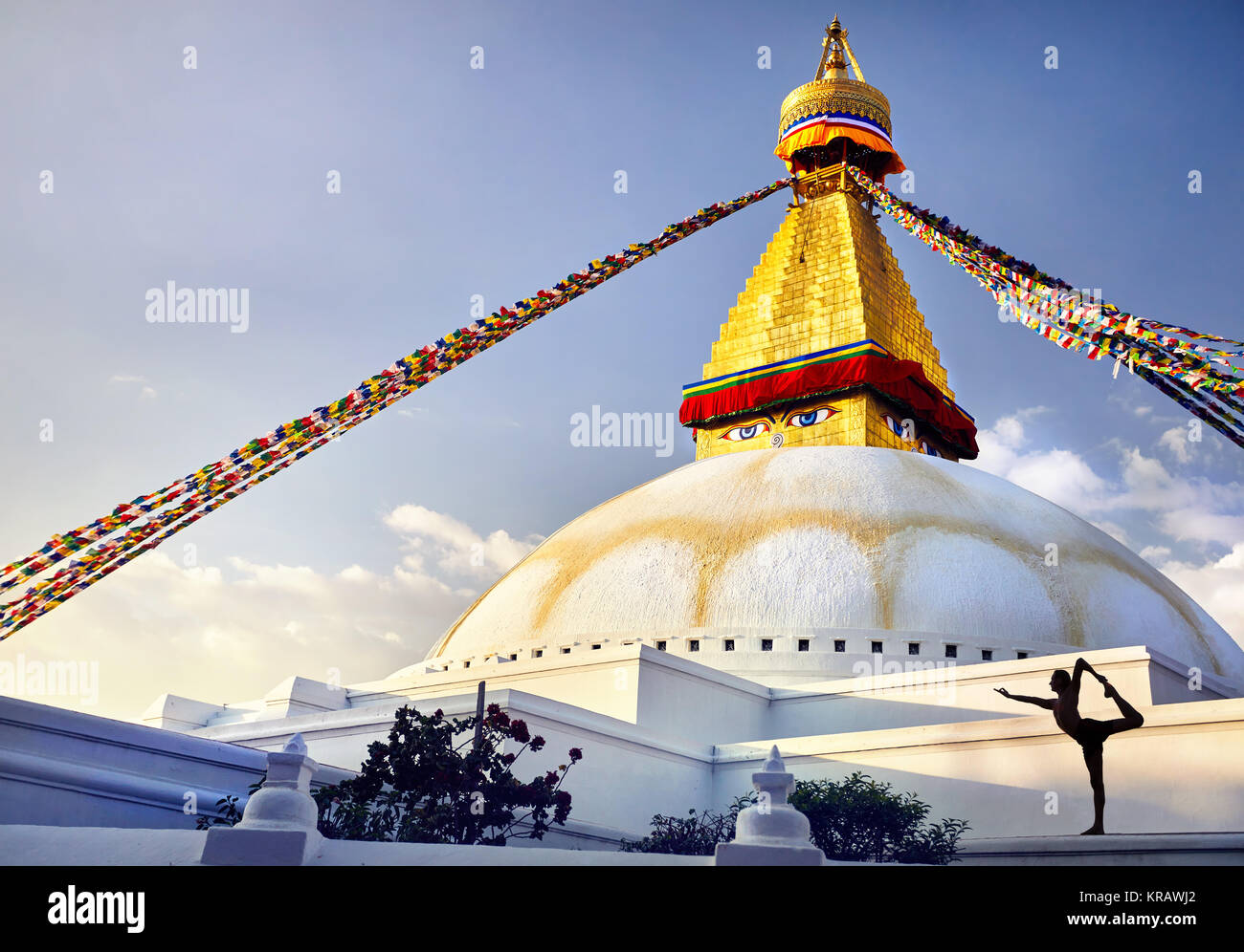 Silhouette of man doing yoga natarajasana at Bodnath Great Buddhist Stupa with prayer flags in Kathmandu - Stock Image