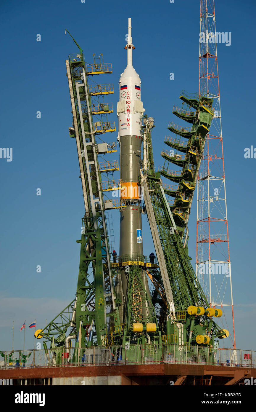 Large gantry mechanisms on either side of the Soyuz TMA-22 spacecraft are raised into position to secure the rocket - Stock Image