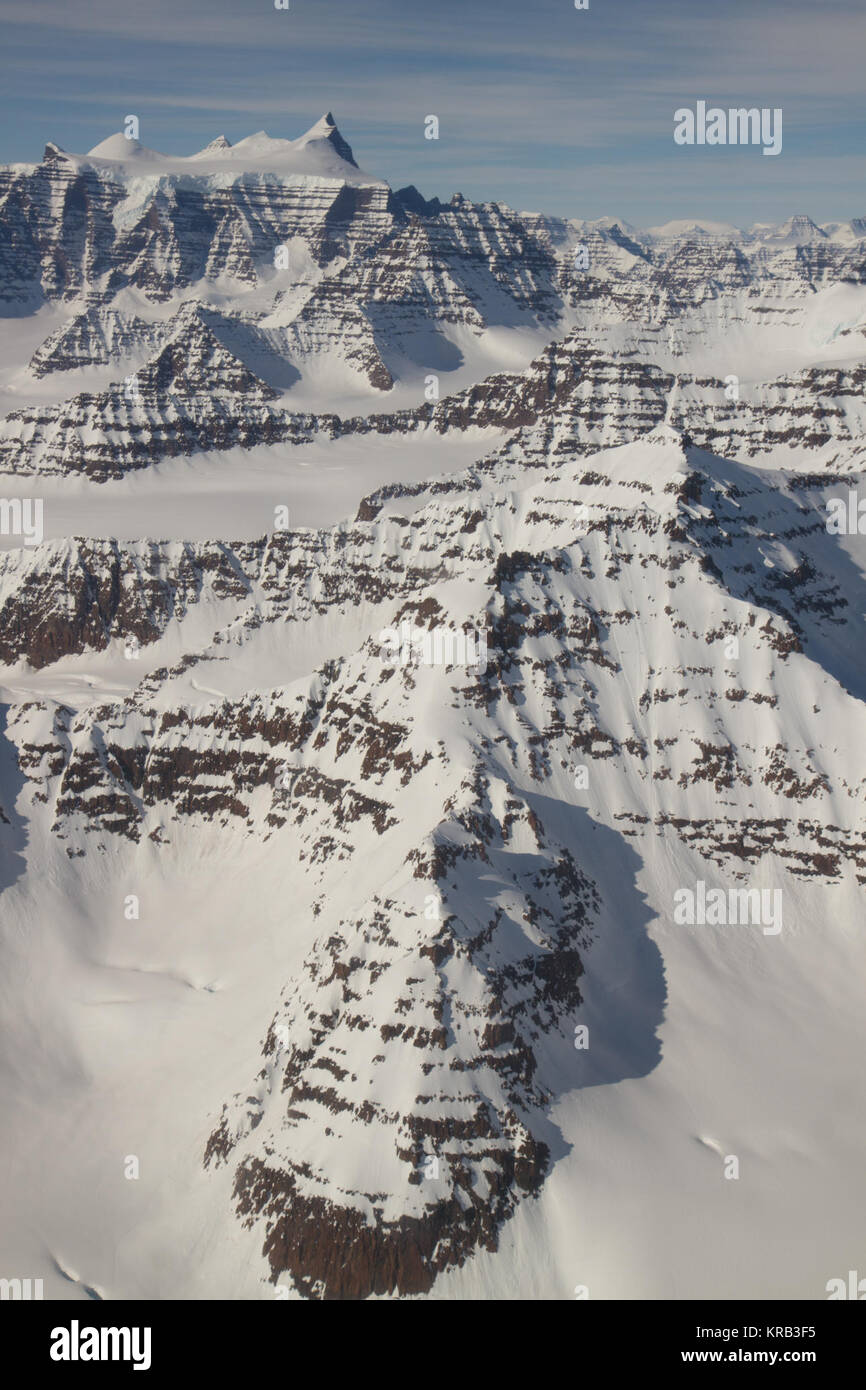 A wider view of mountains showing the distinctive geology of the Geikie Plateau region in eastern Greenland, as - Stock Image