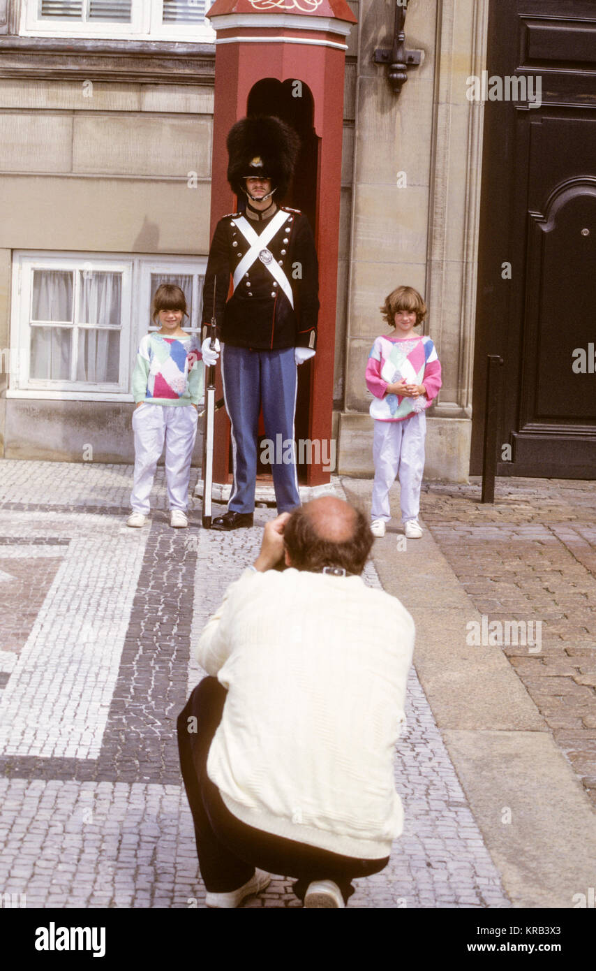 Father photograph daughters with one of the guards men at Amalienborg Castle in Copenhagen 2011 - Stock Image