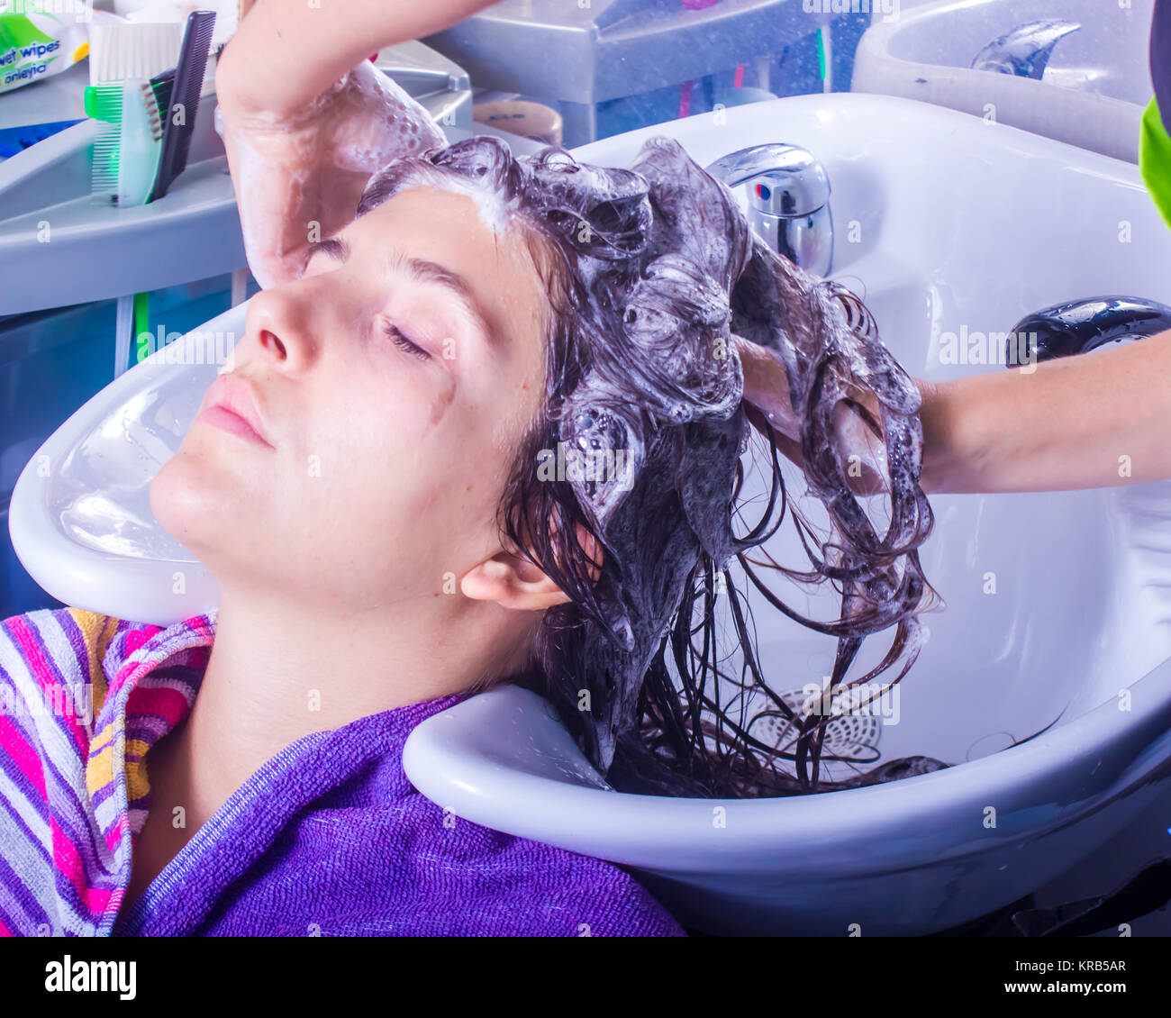 Woman Washing Hair In Hair Salon With Head Backward In The Sink Having Wet  Hair And