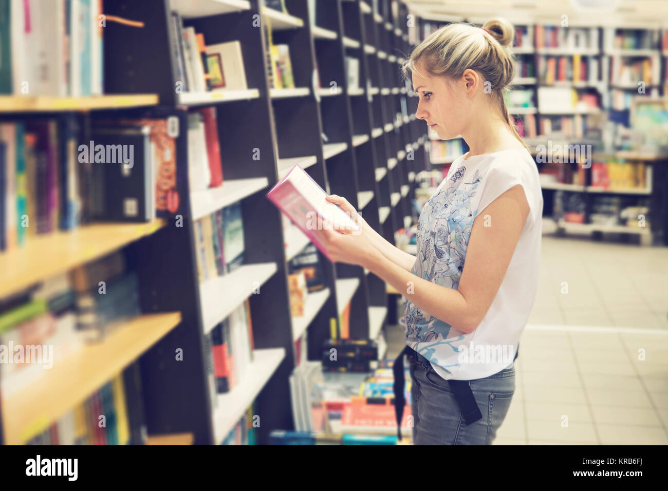 young woman choosing a book to buy in bookstore - Stock Image