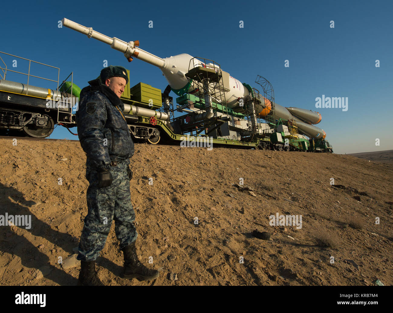 A Russian security guard is seen as the Soyuz rocket is rolled out to the launch pad by train on Tuesday, March - Stock Image