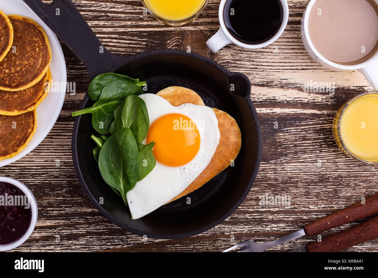 Valentine's day breakfast or brunch. Homemade  heart shape fried egg and pancake in cast iron skillet  with - Stock Image