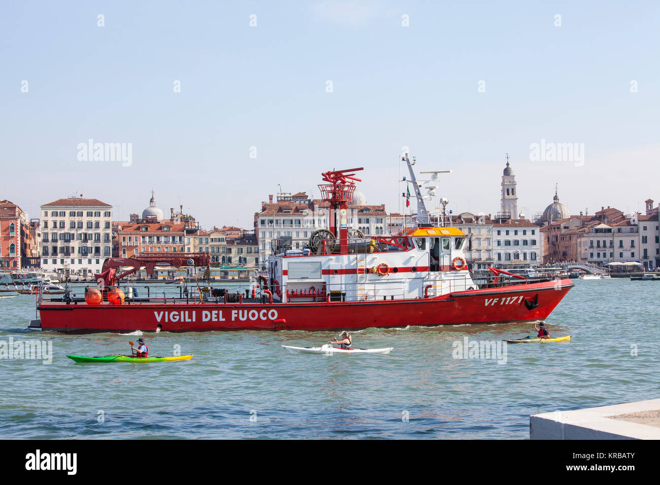 Red Vigili del Fuoco, or firebrigade,  fire tender in Basino San Marco, Venice, Italy with kayakers passing by and - Stock Image