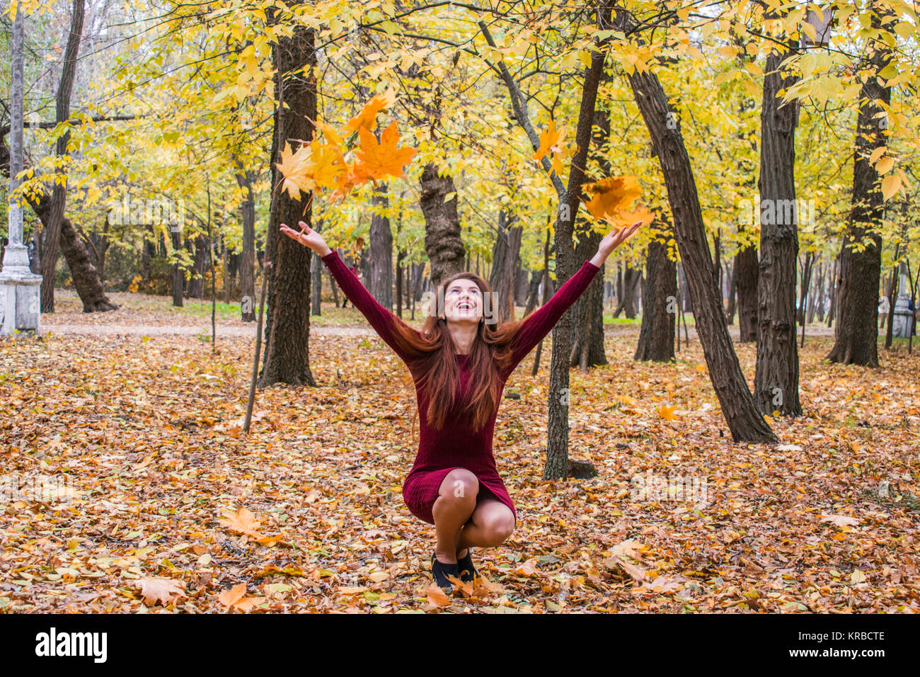 The woman crouched in the park in the fall and throws up yellow leaves. A lot of yellow leaves in the park. Happiness - Stock Image