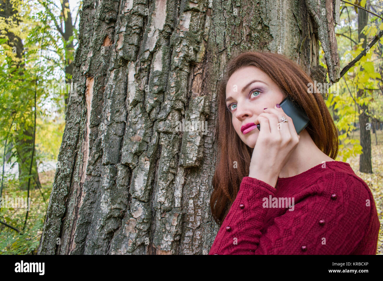 Cute woman in autumn in the park talking on the phone. Woman is standing near the tree Stock Photo