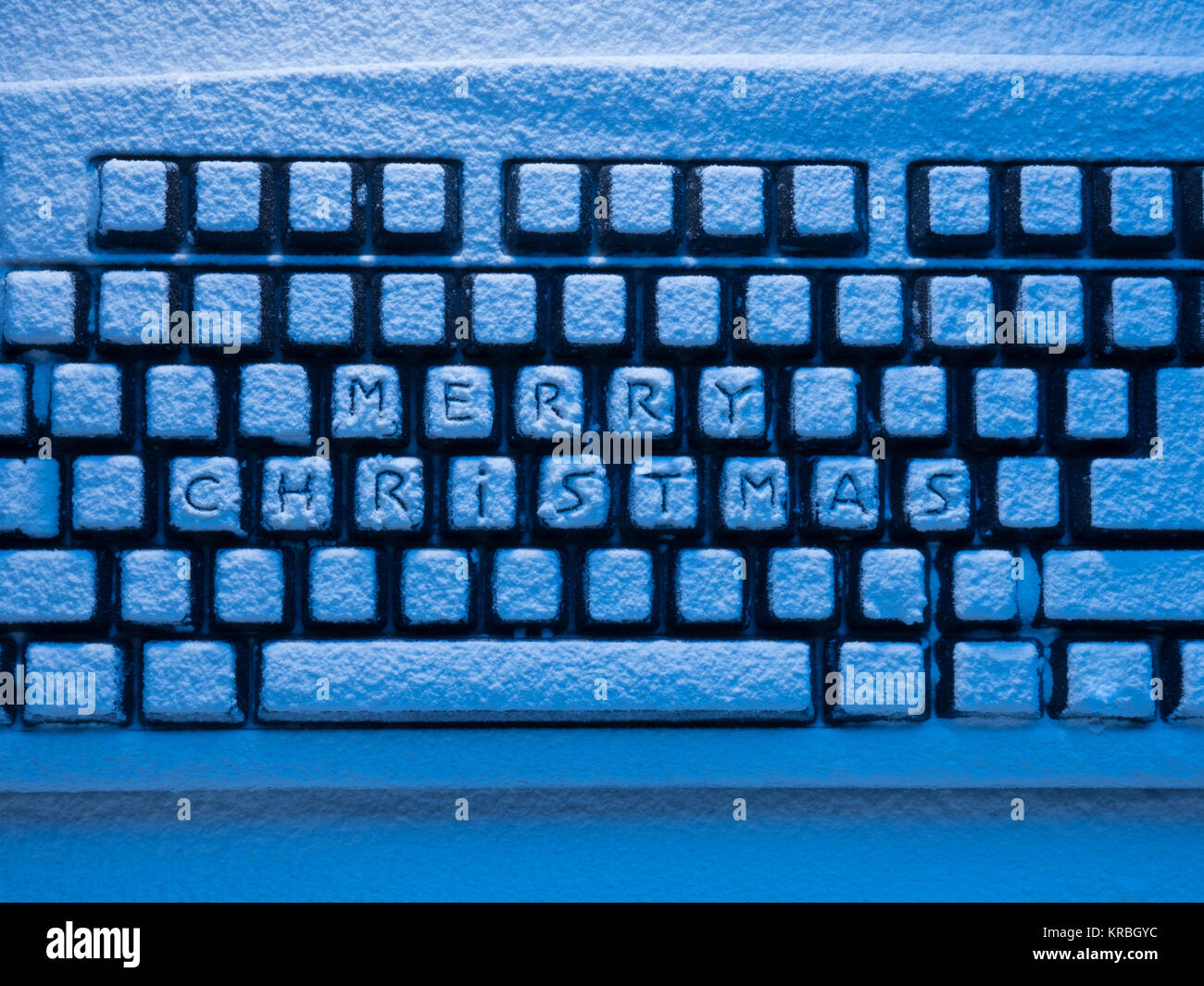 computer keyboard covered with snow illuminated by blue neon light with inscription merry christmas - Stock Image