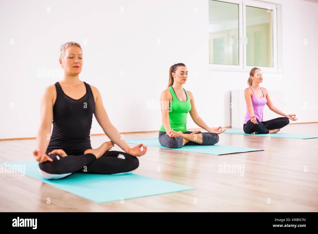 Three girls practicing yoga, Padmasana / Lotus Position - Stock Image