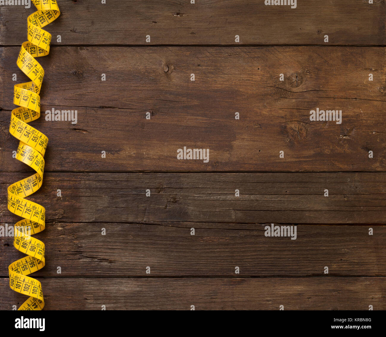 A coiled yellow measuring tape Stock Photo