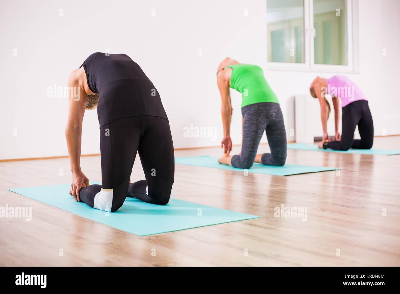 Three girls practicing yoga, Ushtrasana / Camel pose - Stock Image