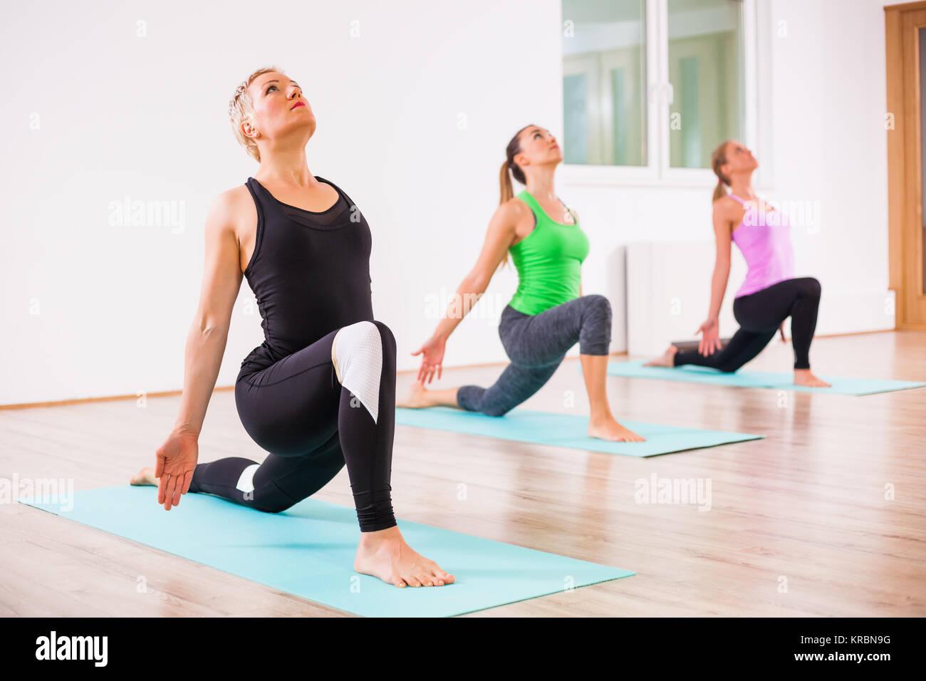 Three girls practicing yoga, Virabhadrasana / Warrior pose - Stock Image