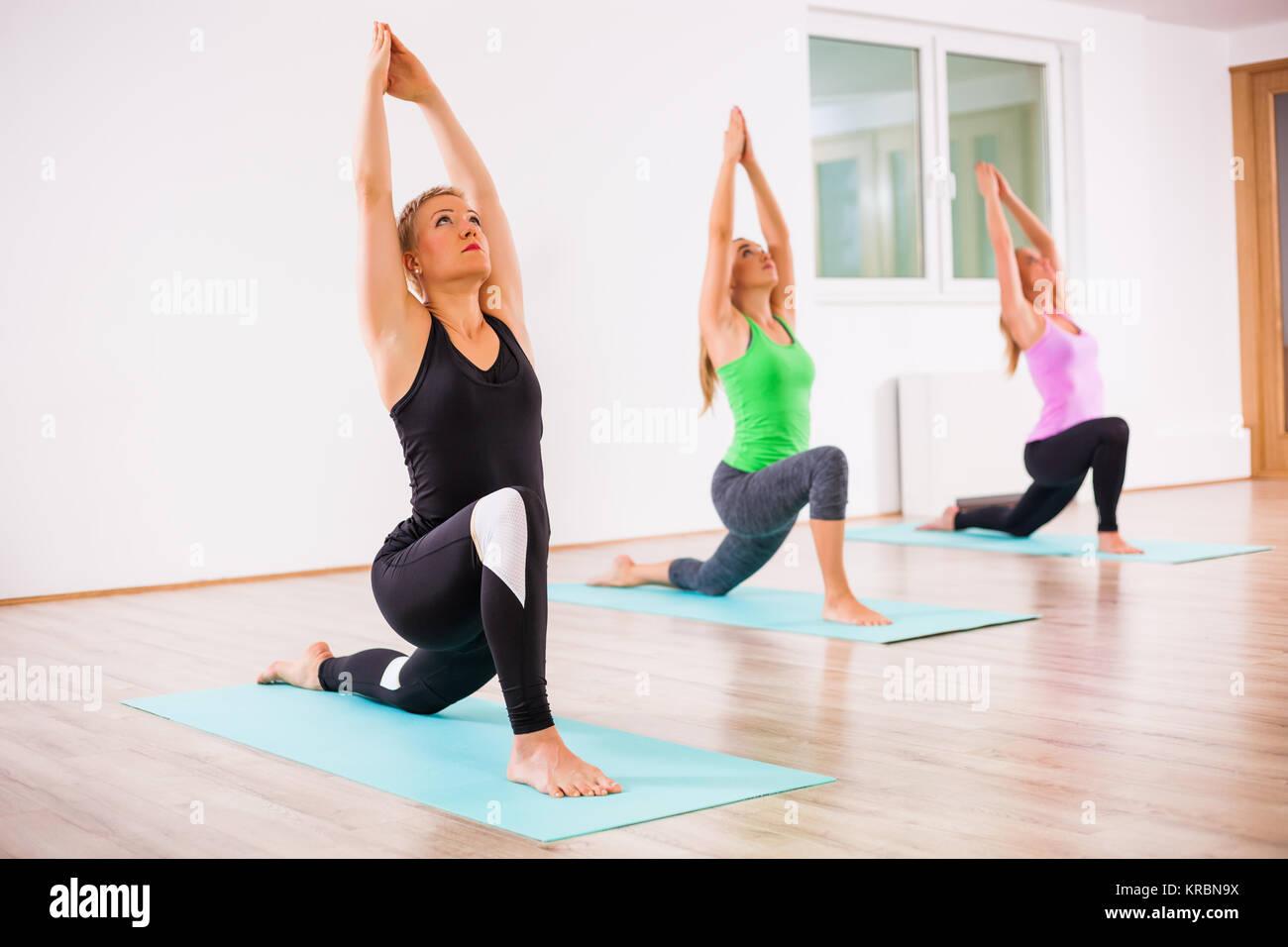 Three girls practicing yoga, Virabhadrasana / Warrior 1 pose - Stock Image