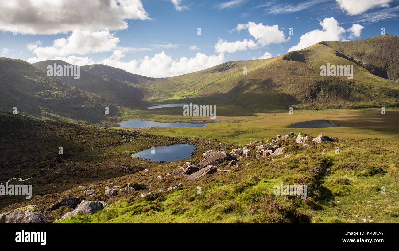 Brandon Mountain, the highest mountain on Ireland's Dignle Peninsula, stands above a deep glacial valley and - Stock Image