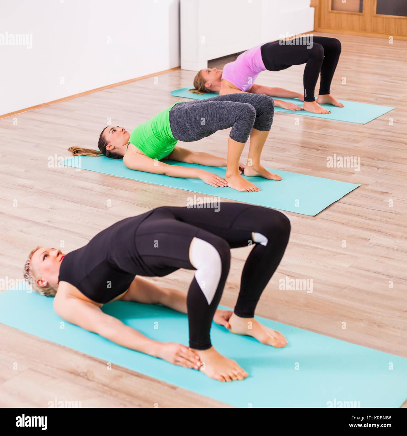 Three girls practicing yoga, Setuasana / Little Bridge pose - Stock Image