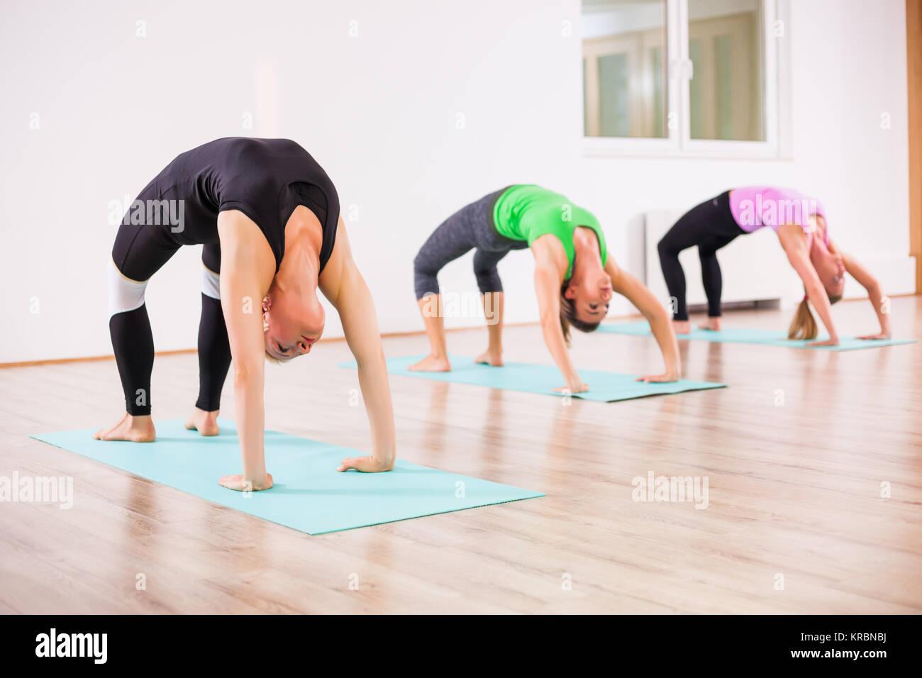 Three girls practicing yoga, Setuasana / Bridge pose - Stock Image