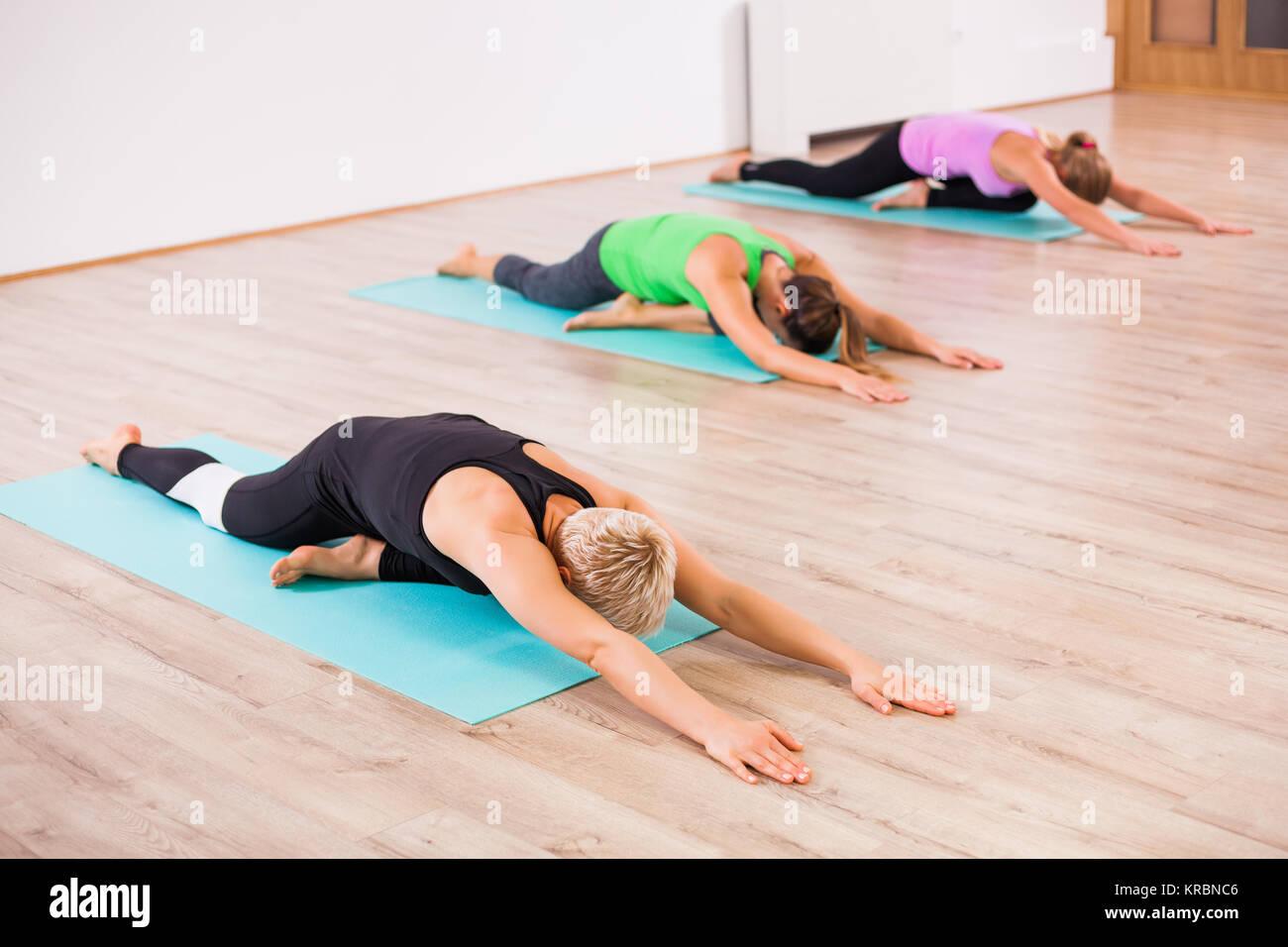 Three girls practicing yoga, Shashankasana / Hare pose - Stock Image