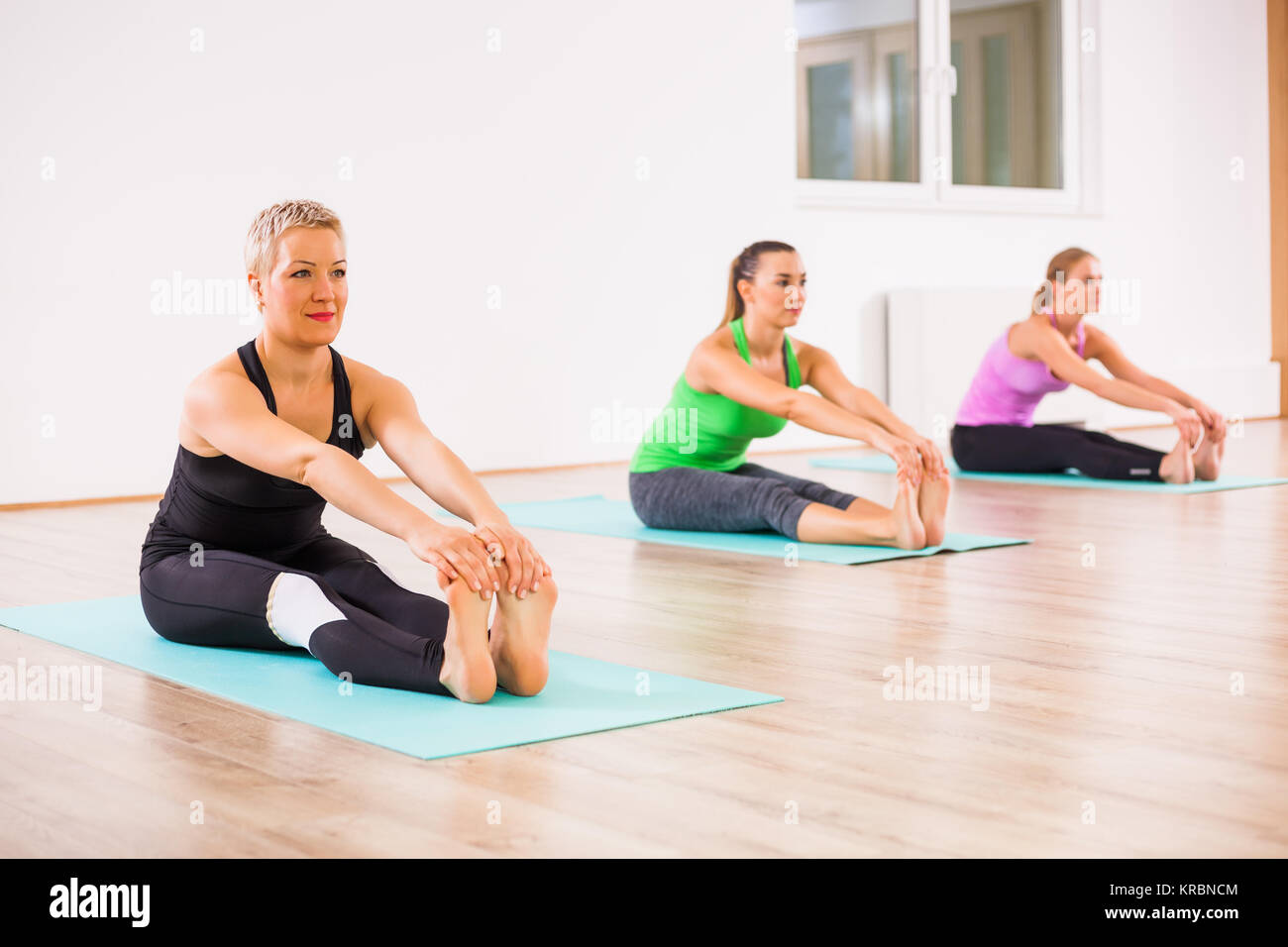 Three girls practicing yoga, Paschimottanasana / Seated Forward Bend pose - Stock Image