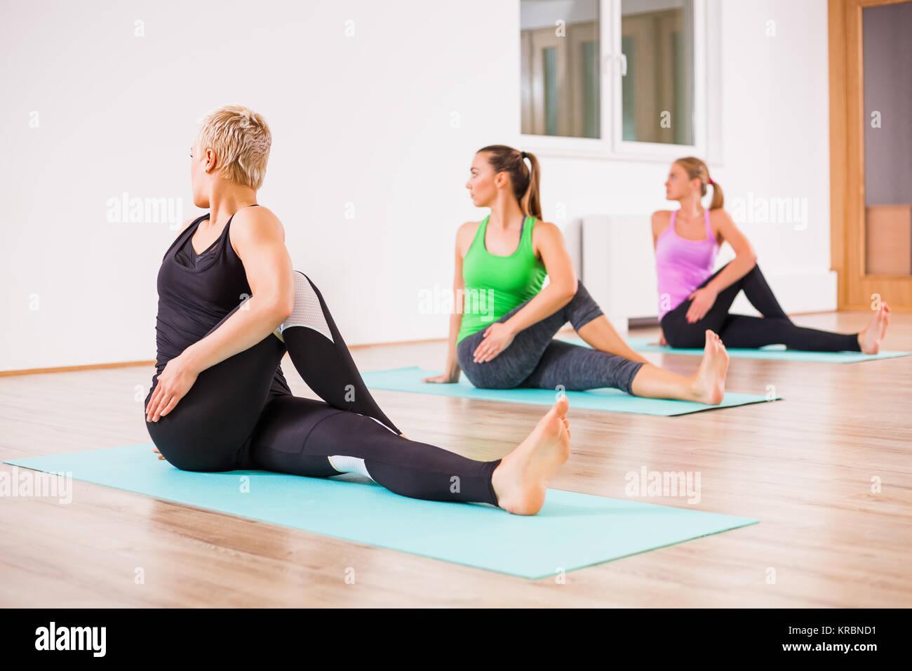 Three girls practicing yoga, Matsyendrasana / Spine-Twisting Pose - Stock Image