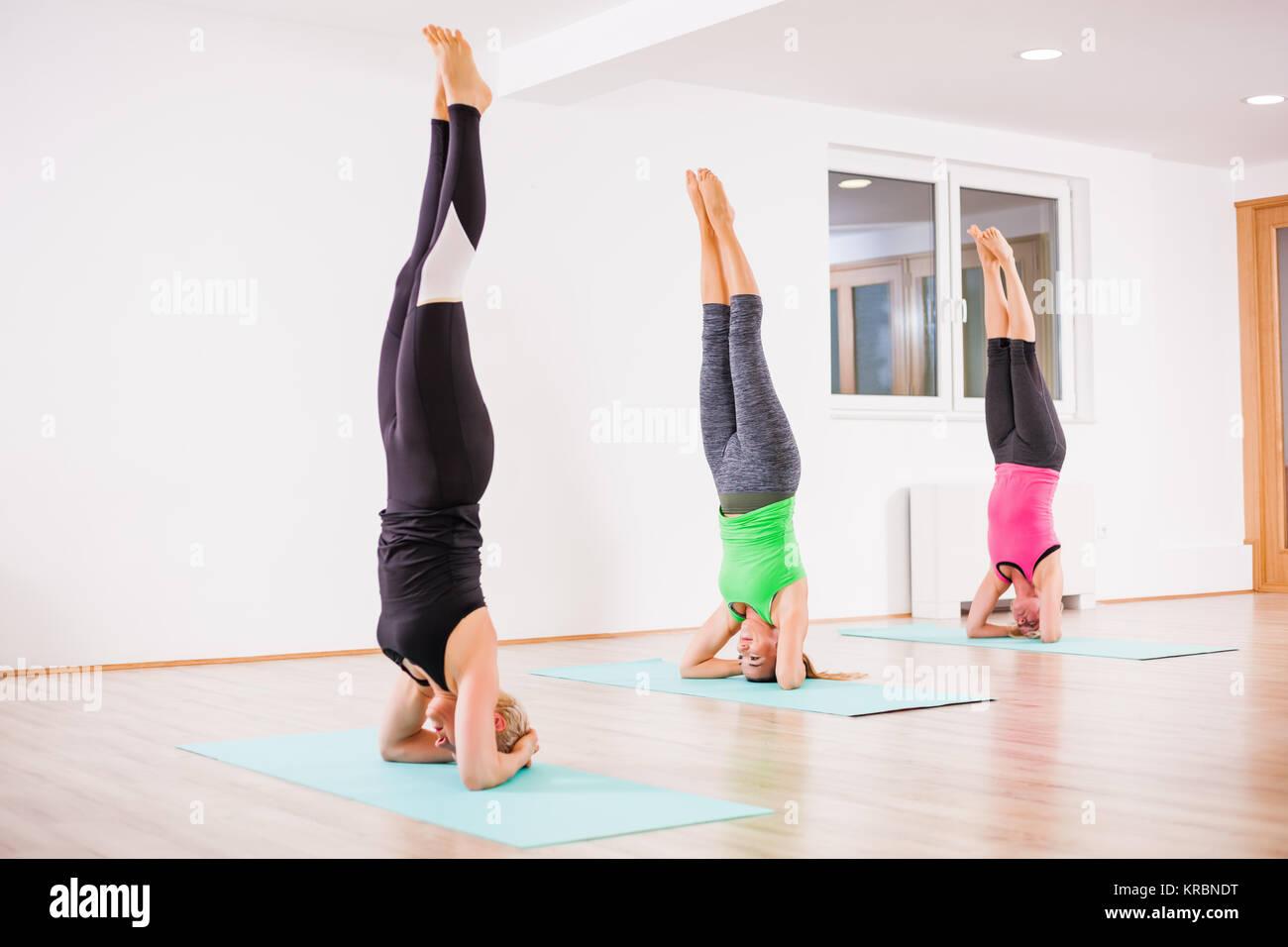 Three girls practicing yoga, Sirsasana / Headstand pose - Stock Image