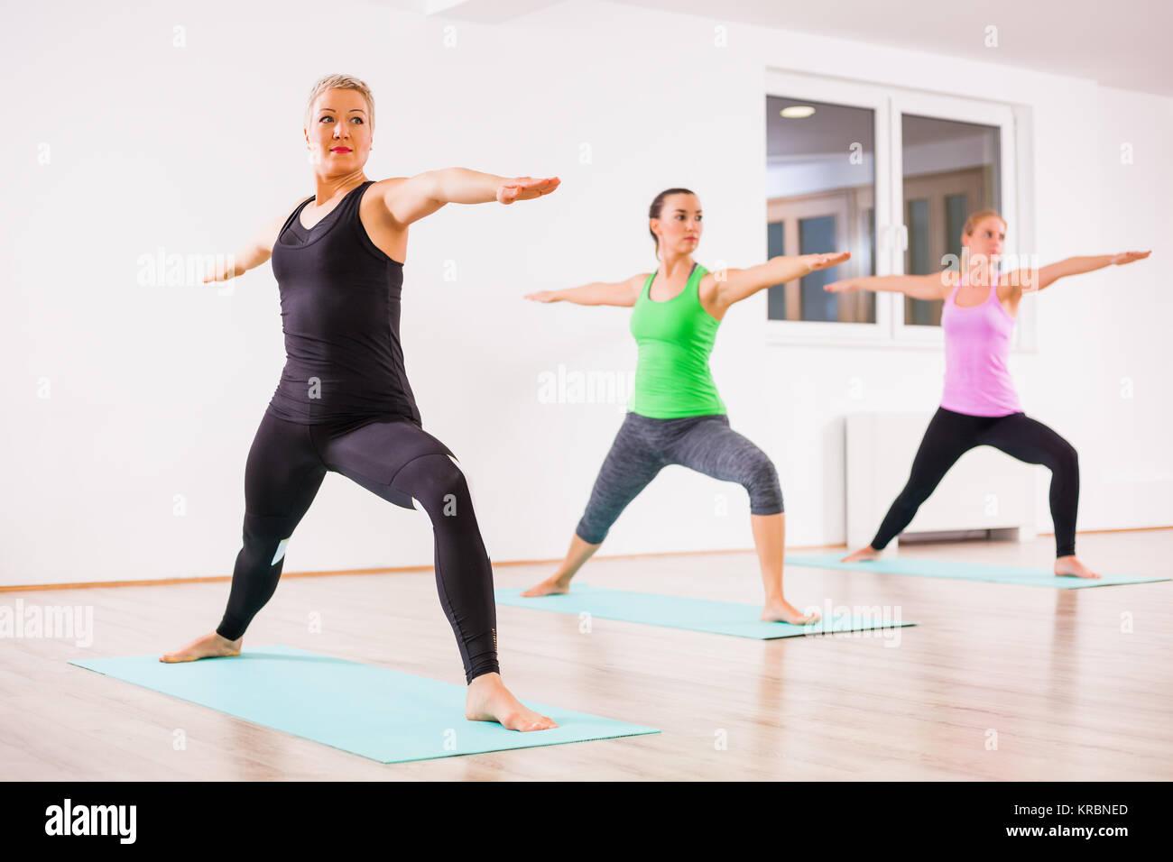 Three girls practicing yoga, Virabhadrasana / Warrior 2 Pose - Stock Image