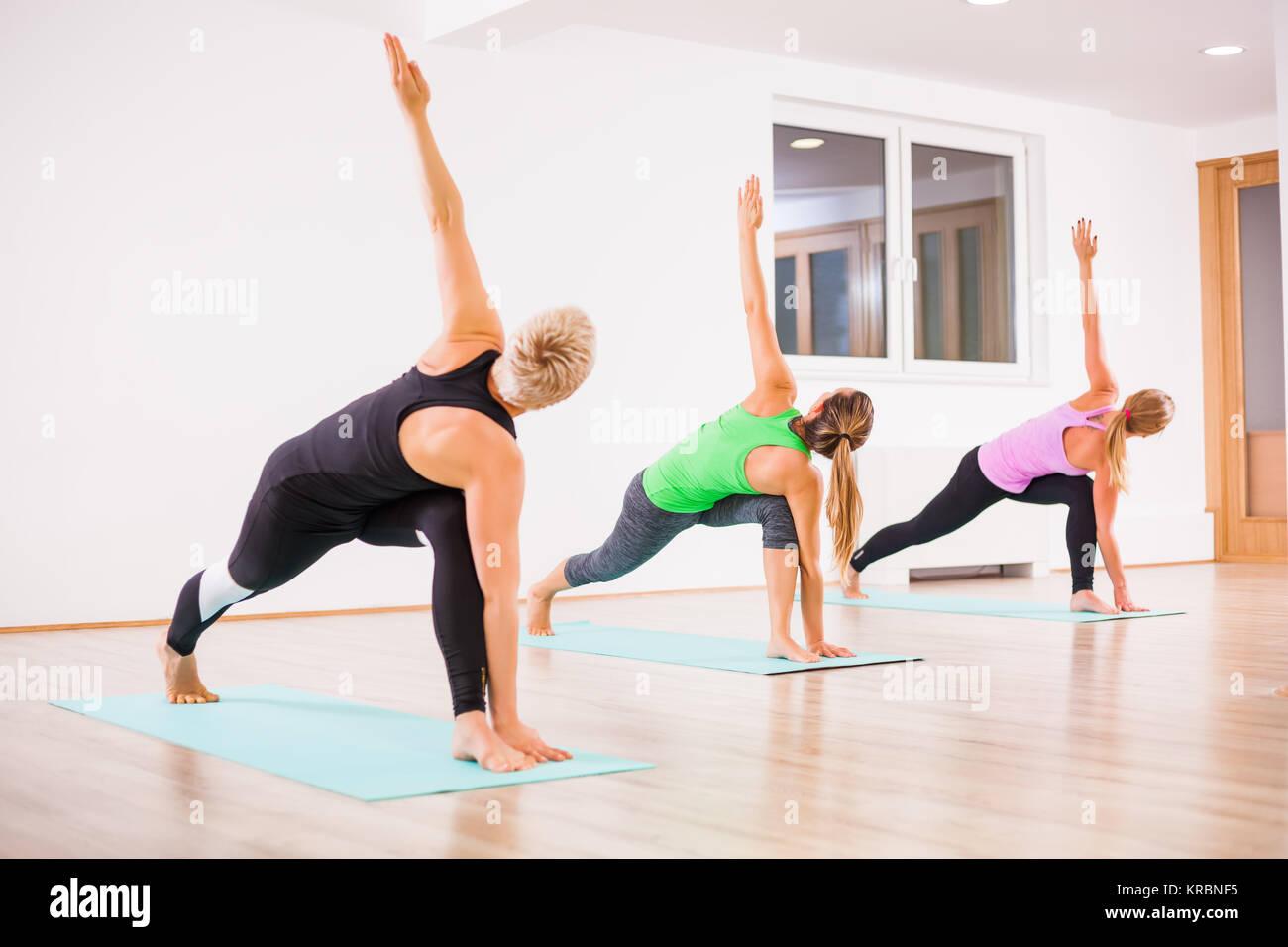 Three girls practicing yoga, Trikonasana / Bikram triangle right pose - Stock Image