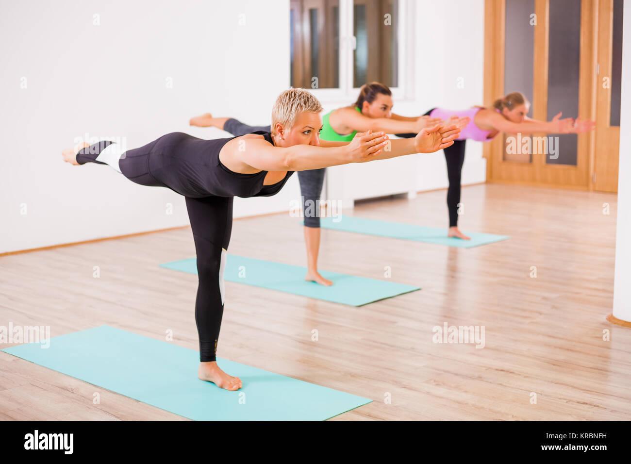 Three girls practicing yoga, Virabhadrasana / Warrior 3 Pose - Stock Image