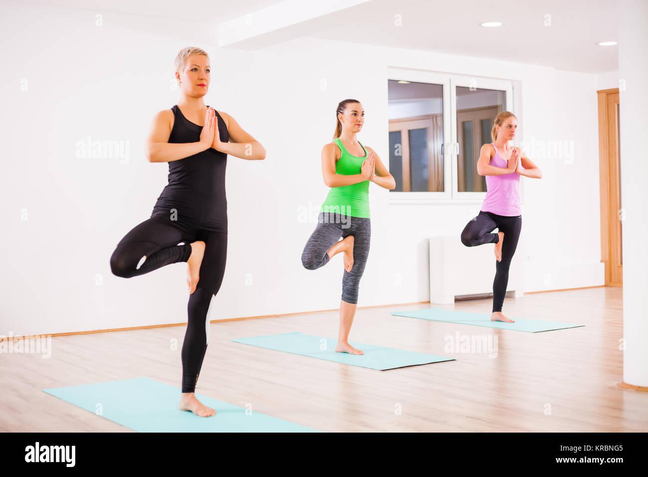 Three girls practicing yoga, Vrikshasana / Tree pose - Stock Image