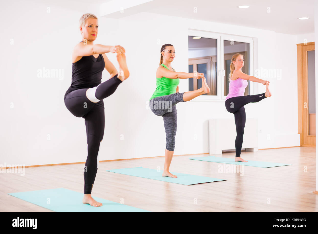 Three girls practicing yoga, Padangusthasana / Hand to big toe pose - Stock Image