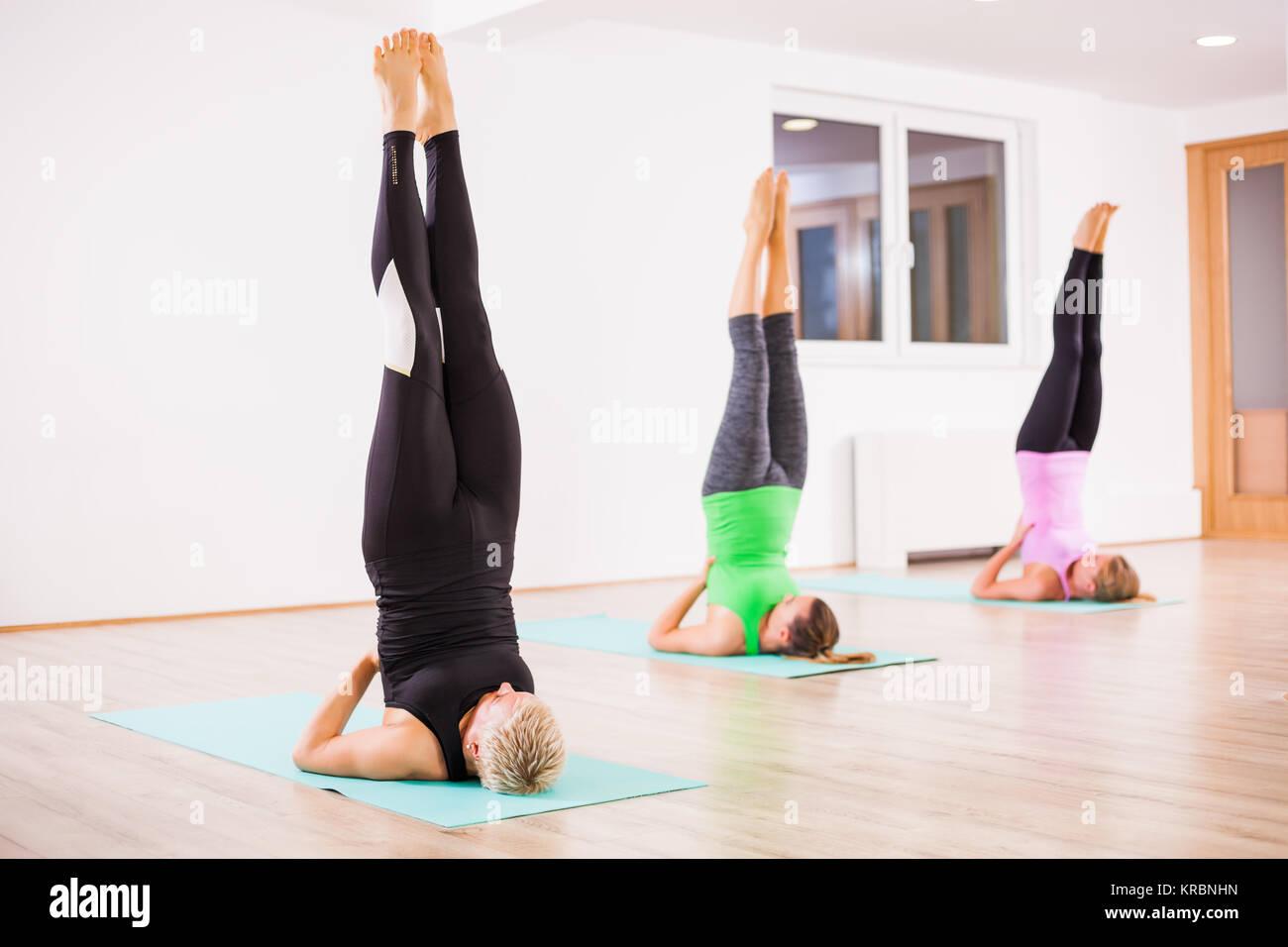 Three girls practicing yoga, Salamba Sarvangasana / Supported shoulder stand - Stock Image