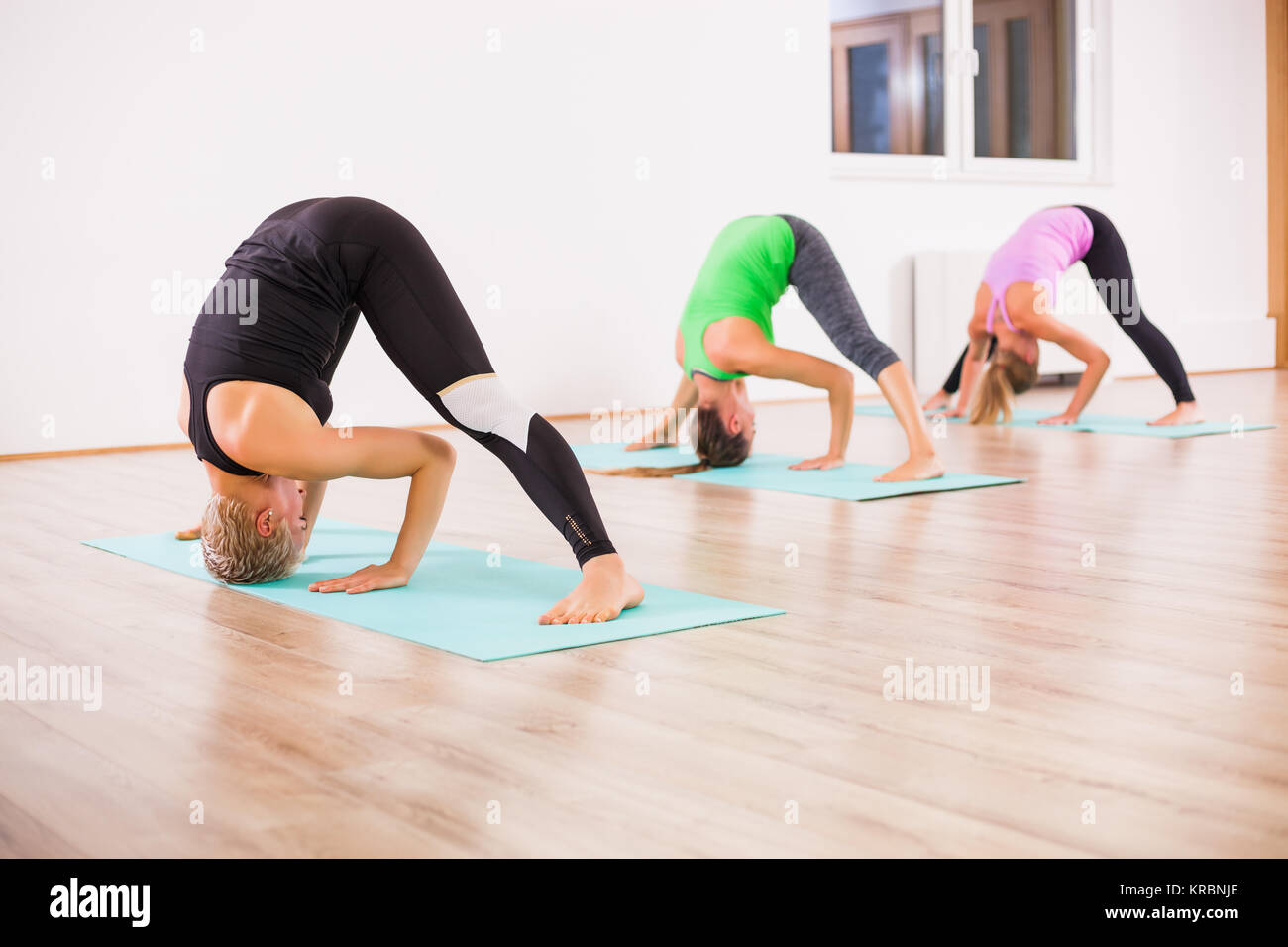 Three girls practicing yoga, - Stock Image