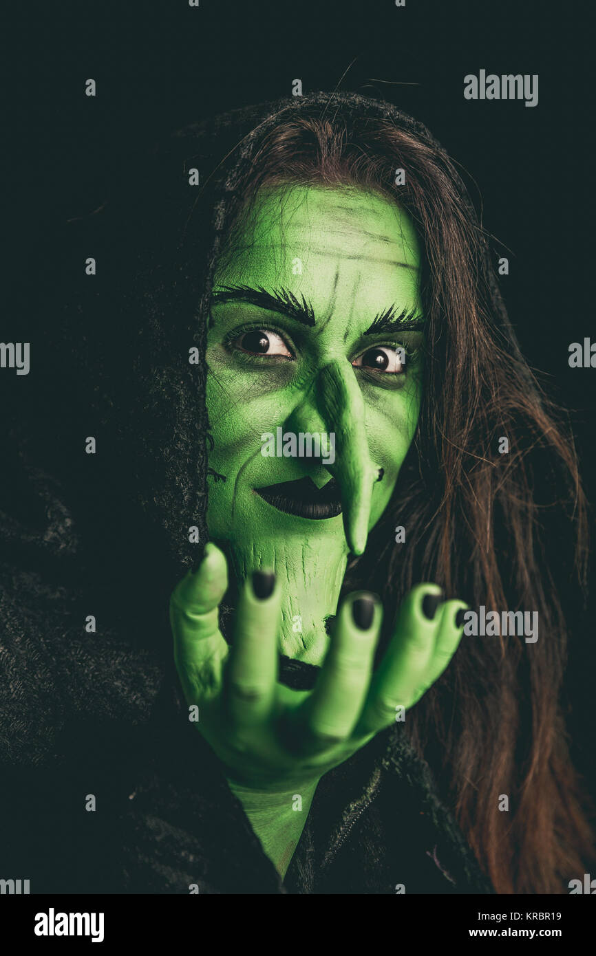 Evil witch holding an invisible item - Stock Image