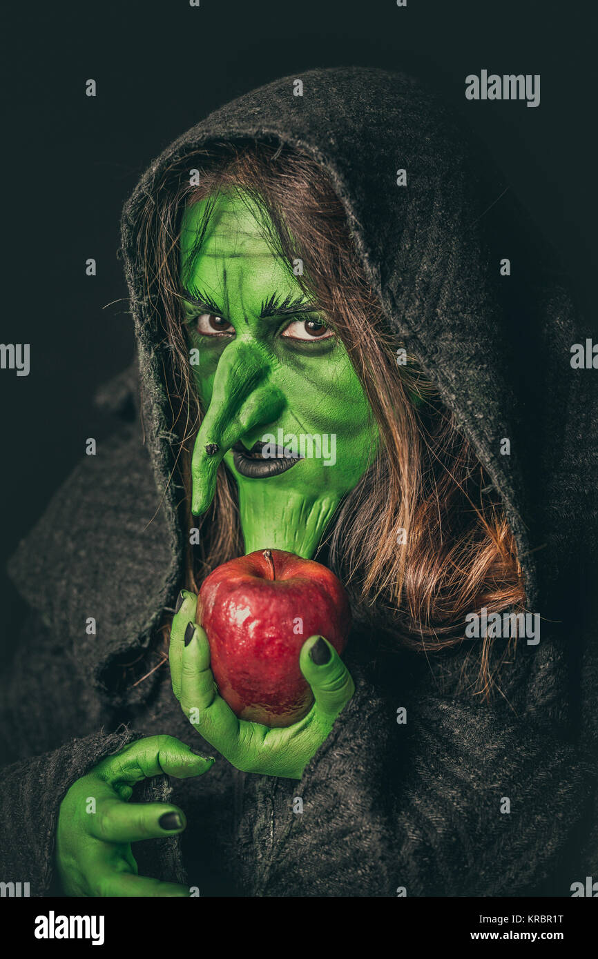 Angry witch with a rotten apple - Stock Image