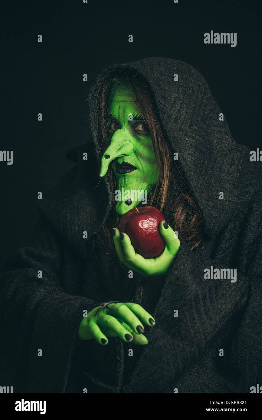 Evil witch with a rotten apple and a spider on her hands - Stock Image