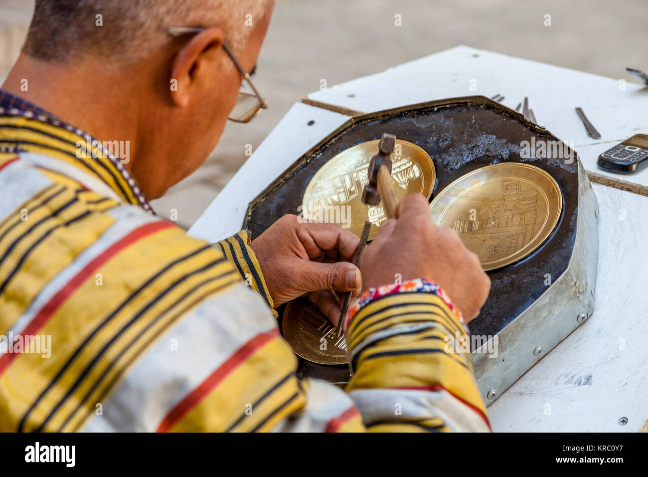 A Local Craftsman In Traditional Dress Engraving A Brass Plate In The Market, Bukhara, Uzbekistan - Stock Image