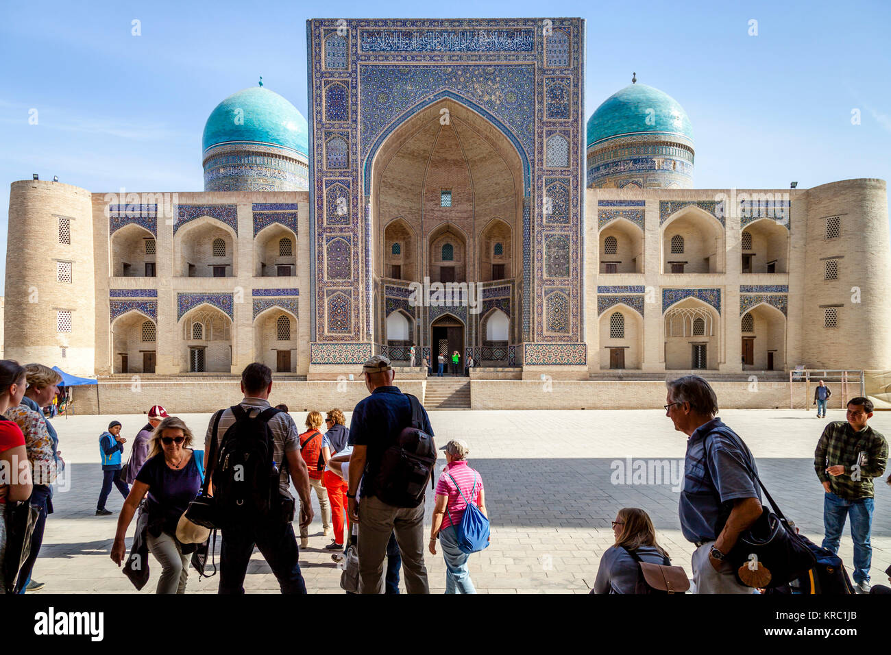 A Group Of Tourists In The Poi Kalyan With The Mir-i-Arab Madrassa In The Backround, Bukhara, Uzbekistan - Stock Image