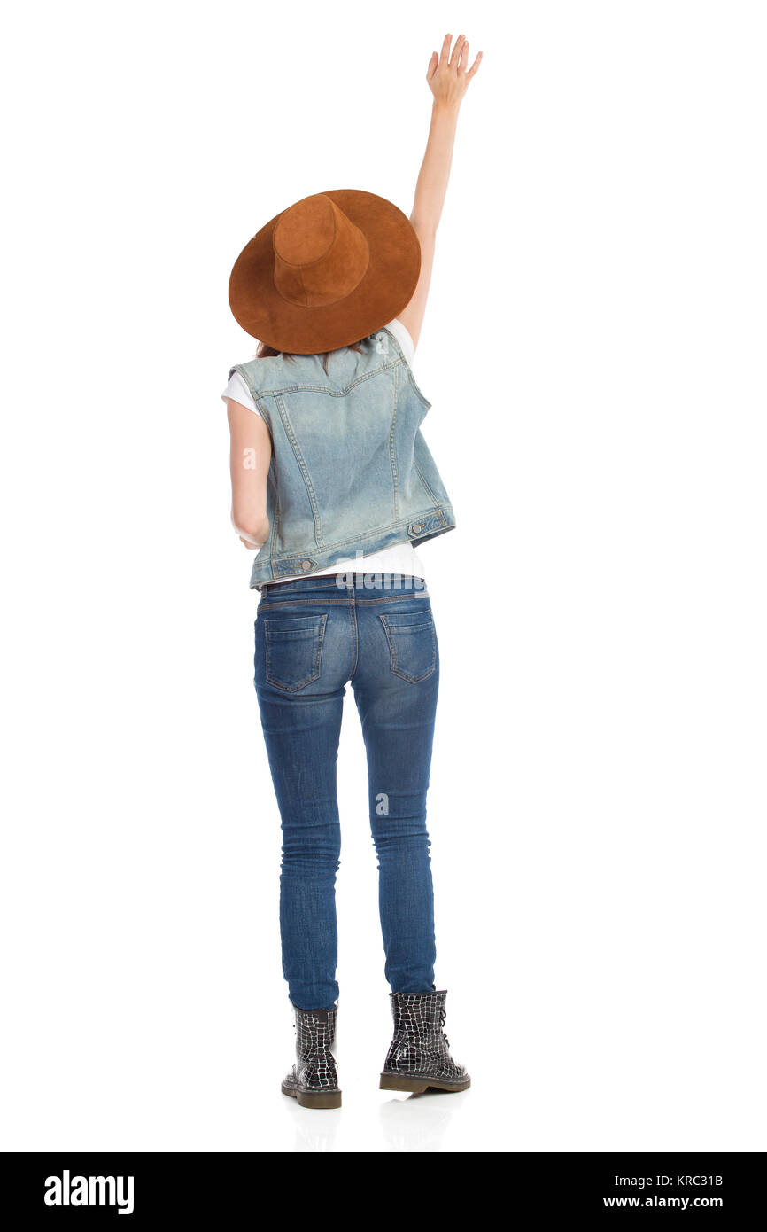 Young woman in jeans vest, black boots and brown suede hat is standing with arm raised and waving hand. Rear view. - Stock Image