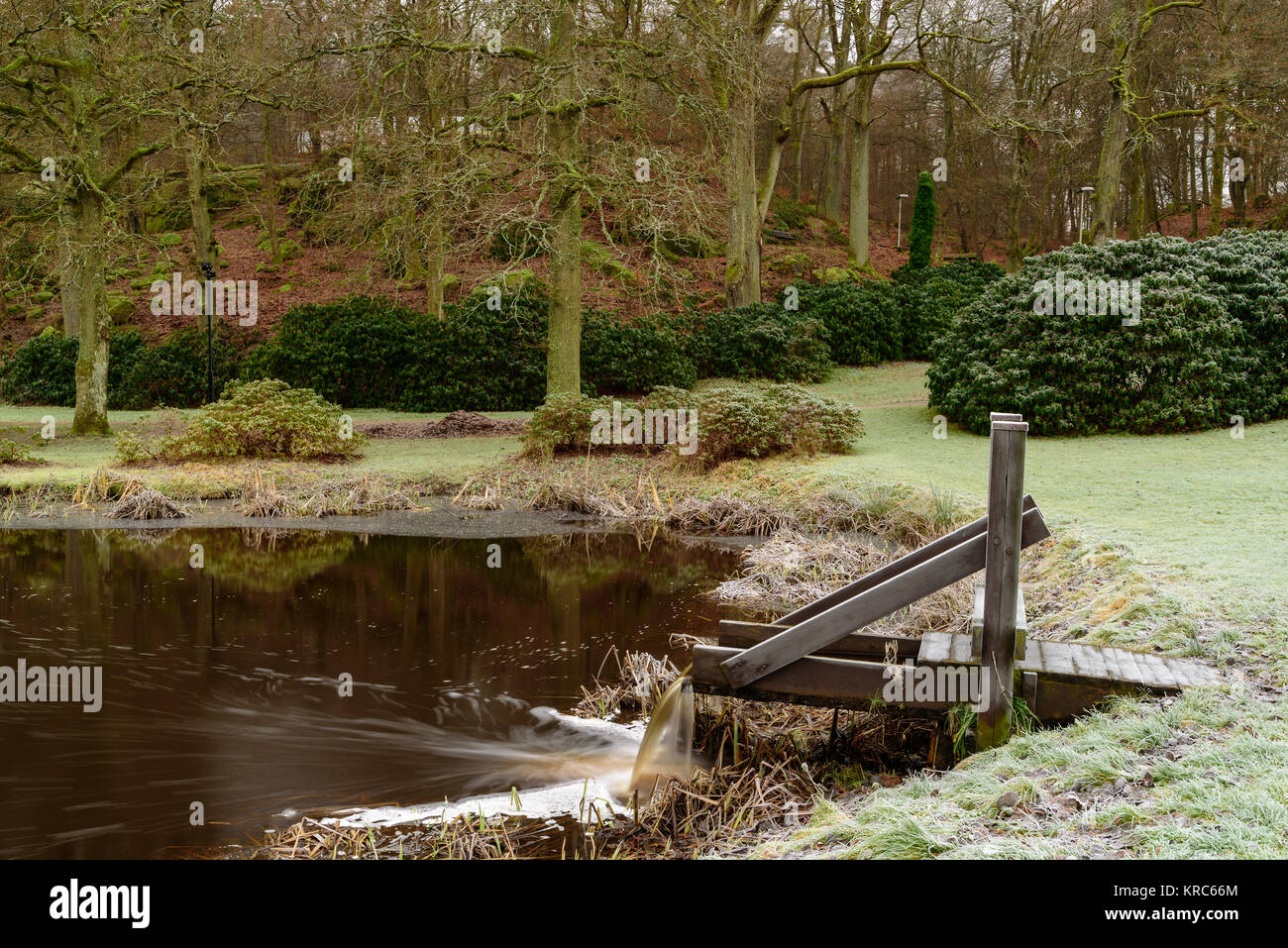 Wooden Waterfall Pouring Water Into Pond In Public Park Woodland