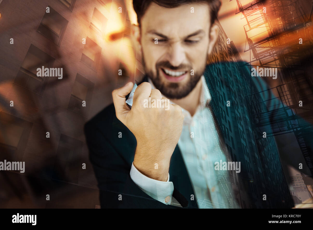 Furious businessman sitting at the table - Stock Image