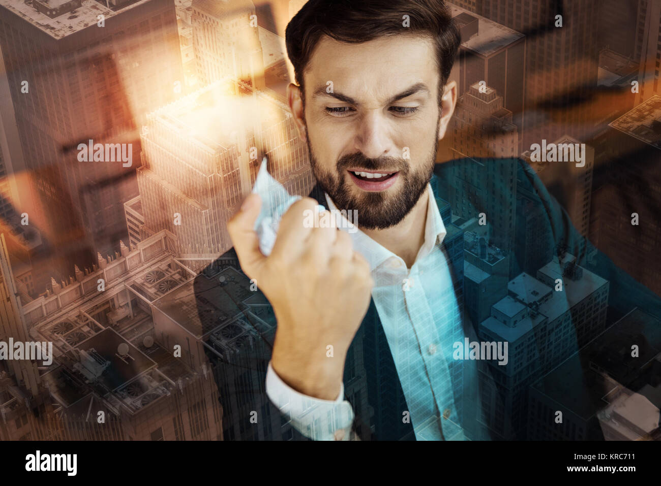 Irritated man in suit squeezing paper in his hands - Stock Image