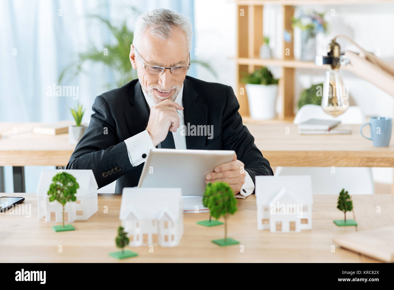 Cheerful real estate agent smiling while looking at the tablet - Stock Image
