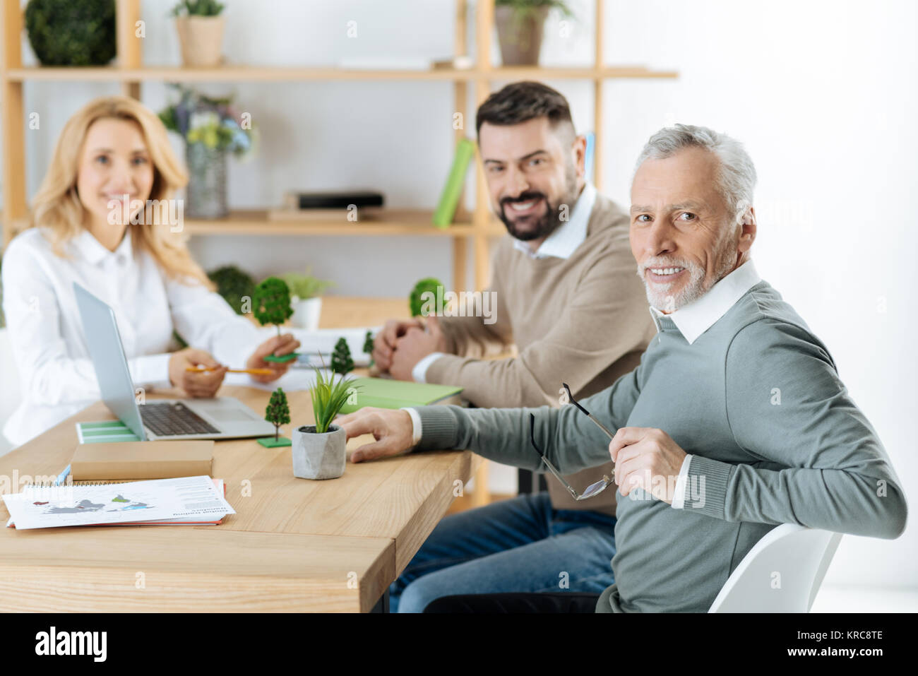 Creative positive engineers smiling while having an important meeting - Stock Image