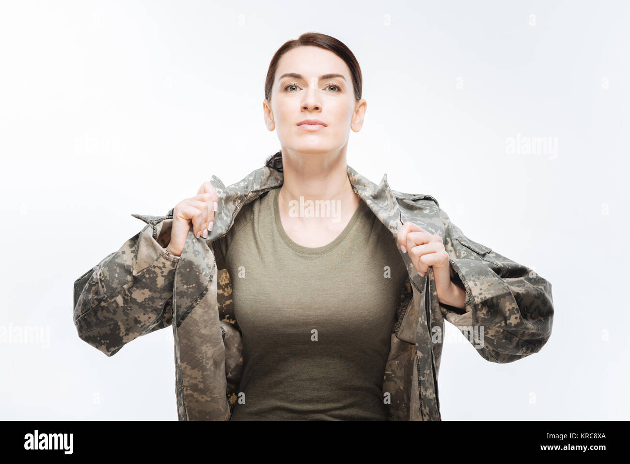 Earnest ambitious woman taking on uniform - Stock Image