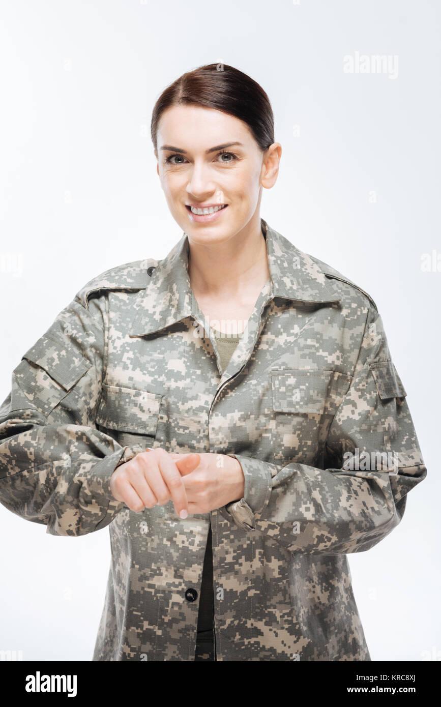 Cheerful cute woman zipping combat uniform - Stock Image