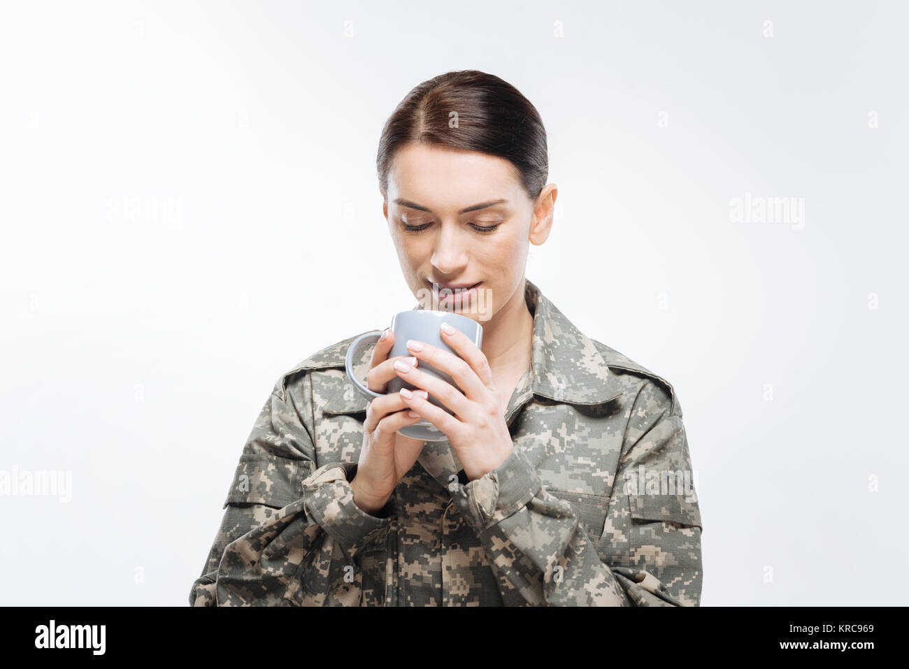 Calm female soldier enjoying coffee - Stock Image