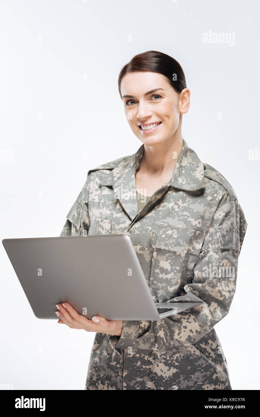 Happy female soldier working with laptop - Stock Image